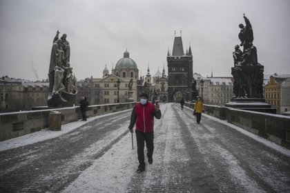 Un hombre camina bajo la nieve en el Puente Carlos de Praga, en República Checa. Michal Cizek / AFP