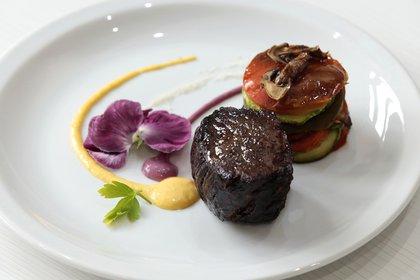 Lomo cocinado a gusto con salsa de vino tinto con hongos de pino, champinñones acompañado de morrones, pepino y zanahoria al vapor.
