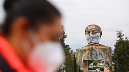 A banner fashioned to resemble a giant protective mask is placed on a monument of Benito Juarez, as a message to the community to fight against the spread of the coronavirus disease (COVID-19), in the Iztapalapa neighbourhood, one of the highly contagious zones, in Mexico City, Mexico, August 13, 2020. REUTERS/Edgard Garrido