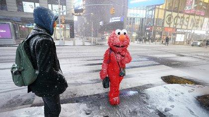Una persona con un disfraz de Elmo se encuentra bajo la nieve en Times Square en la ciudad de Nueva York, el 16 de diciembre de 2020 (Foto de TIMOTHY A. CLARY / AFP)