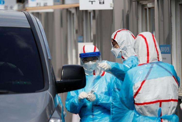 FOTO DE ARCHIVO: Personal médico con equipo de protección se prepara para tomar muestras de los visitantes en sus coches en un centro de pruebas del COVID-19 en el Centro Médico de la Universidad de Yeungnam, en Daegu, Corea del Sur, 3 de marzo de 2020. REUTERS/Kim Kyung-Hoon/Archivo Foto