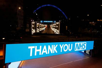 FILE PHOTO: Wembley stadium is seen lit up blue for the Clap For Our Carers campaign in support of the NHS, as the spread of the coronavirus disease (COVID-19) continues, London, Britain, March 26, 2020. REUTERS/Matthew Childs