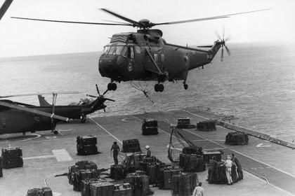 La flota británica cruza el océano. Un helicóptero Sea King sobrevuela el portaviones Hermes para transportar munición y distribuirla entre otros barcos, abril de 1982 (Martin Cleaver/Pool/Getty Images)