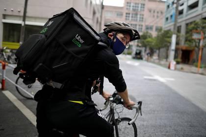 El medallista olímpico de esgrima japonés Ryo Miyake pedalea mientras trabaja a tiempo parcial como repartidor de Uber Eats bajo un estado de emergencia nacional mientras la propagación de la enfermedad coronavirus (COVID-19) continúa en Tokio, Japón, el 12 de mayo de 2020 (REUTERS/Issei Kato)
