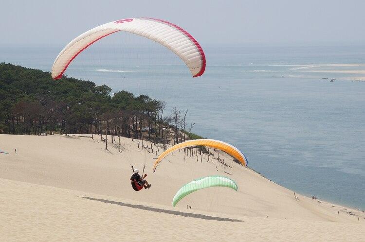 Las enormes dunas de Pyla-sur-Mer, en la costa francesa, no sólo invitan a sus playas, sino a los deportes de aire, como el parapente.