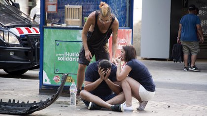Varios jóvenes permanecen junto a los restos de un vehículo, en el lugar del atropello (EFE)