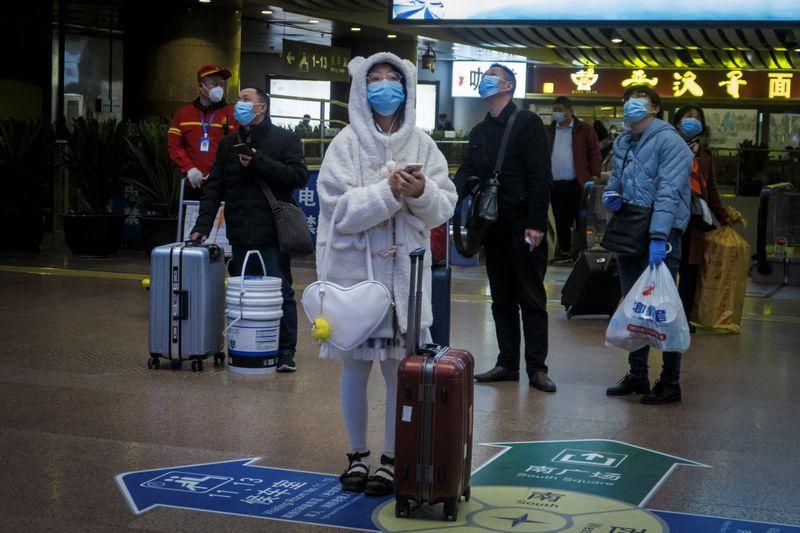 Viajeros usan mascarilla en una estación de trenes luego del brote de coronavirus en Pekín (REUTERS/Thomas Peter)