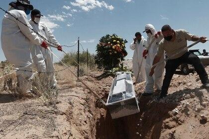 Trabajadores de un cementerio entierran a una víctima del coronavirus en una zona especial dedicada a los afectados por la enfermedad, en Ciudad Juárez, México (AP)