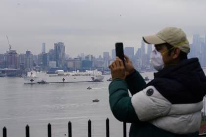 Un hombre registra la llegada a Nueva York del buque hospital USNS Comfort (Reuters)