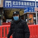 A police officer stands guard outside of Huanan Seafood Wholesale market where the coronavirus was detected in Wuhan on January 24, 2020. - The death toll in China's viral outbreak has risen to 25, with the number of confirmed cases also leaping to 830, the national health commission said. (Photo by Hector RETAMAL / AFP)