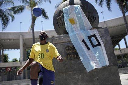 """Marcio Pereira, de 57 años y quien se hace apodar """"Pelé"""", domina el balón junto a un monumento adornado con una bandera argentina y con el 10 de Diego Maradona frente al estadio Maracaná en Río de Janeiro, el jueves 26 de noviembre de 2020 (AP Foto/Silvia Izquierdo)"""