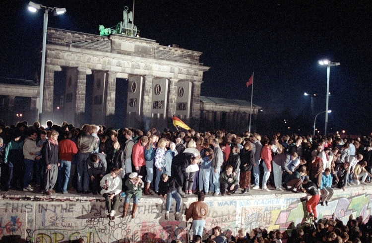 El 10 de noviembre de 1989, los ciudadanos de Alemania Oriental y Occidental celebran subidos al muro de Berlín en la puerta de Brandenburgo tras el anuncio de la apertura de la frontera de Alemania Oriental (Foto: Martti Kainulainen/Shutterstock (503486f)).