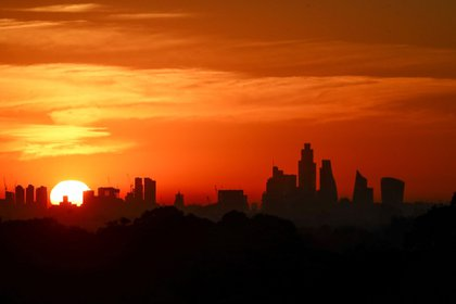 The sun rises over the skyline in this view from Richmond Park in London, U.K., on Friday, July 31, 2020. London's best offices are forecast to plunge in value by as much as 15% this year as the coronavirus hits rents and investors' appetite for real estate. Photographer: Simon Dawson/Bloomberg