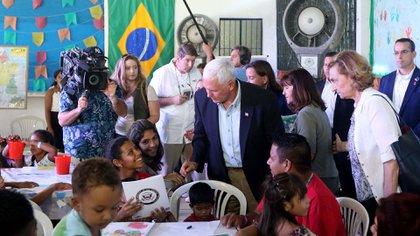 Mike Pence junto a refugiados venezolanos en Brasil (AFP)