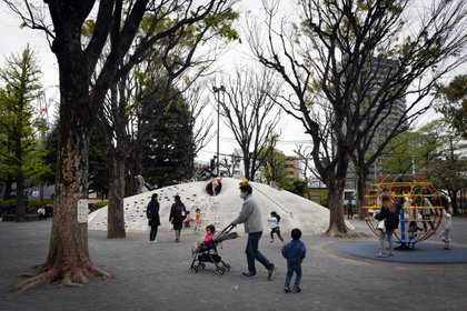 "FILE -- Children play in a park in Tokyo on April 17, 2020. A new website in Japan, DQN Today, describes itself as a crowdsourced guide to help house hunters avoid neighborhoods inhabited by ""stupid parents who let their children play on roads and parking lots."" (Noriko Hayashi/The New York Times)"