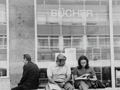 Dos estudiantes leen frente a una librería en los alrededores de la Universidad de Leipzig (Photo by Michael Nitzschke Shutterstock)