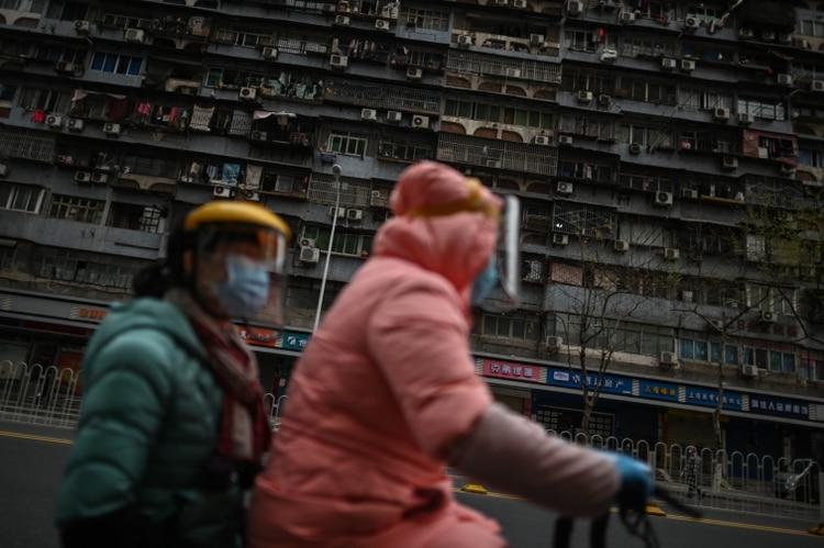 Dos mujeres en una moto en Wuhan (Hector RETAMAL / AFP)