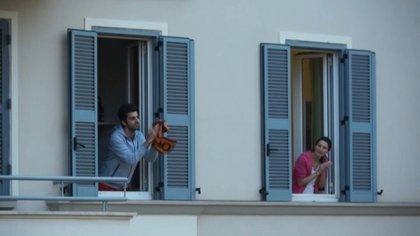 Los italianos intentan superar el aislamiento social impuesto por el bloqueo del coronavirus del país saliendo a sus balcones y cantando al unísono (AFP)