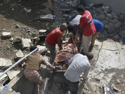 Socorristas trasladan a una de las víctimas (AP)
