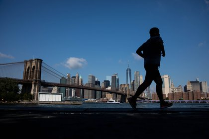 A jogger runs along the water in the Dumbo neighborhood in the Brooklyn borough of New York, U.S., on Friday, Sept. 4, 2020. U.S. stocks fell to a two-week low as megacap tech shares came under pressure for a second day, but came off their lows as the holiday weekend approached.