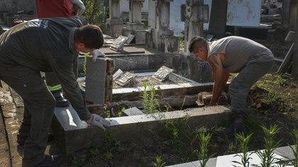 Dos jóvenes sepultureros llevan adelante una exhumación. Foto: Fernando Calzada.