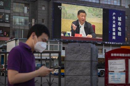 Un hombre pasa frente a una pantalla que trasmite un discurso del presidente chino Xi Jinping en Beijing este martes. (AP/Mark Schiefelbein)