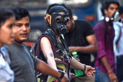Una joven con una máscara de gas participa en una protesta contra la inacción gubernamental ante el colapso del clima y la contaminación ambiental, parte de las manifestaciones que se llevaron a cabo en todo el mundo (Foto de Biju BORO / AFP)