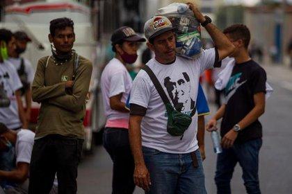Un sujeto viste una camiseta con la cara de Alex Saab y carga una bolsa de comida como pago por asistir a un evento organizado por la dictadura de Maduro
