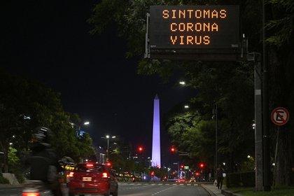 El obelisco de Buenos Aires es visto con un cartel que advierte del COVID-19 (AFP)