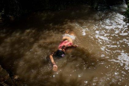 """Una niña se baña en una quebrada llamada """"La Poza"""", en Caracas (EFE/ Miguel Gutiérrez)"""