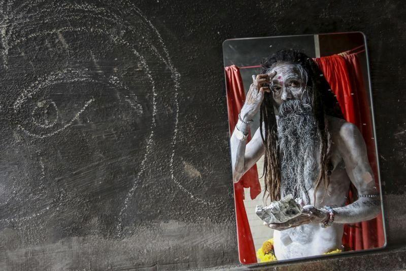 Un sadhu naga, o un hombre santo hindú, se aplica ceniza en su campamento antes de una procesión durante el Kumbh Mela o el Festival de la Jarra en Trimbakeshwar, India, 27 de agosto de 2015.
