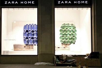 Un hombre sin techo lee un libro junto a una tienda de Zara Home, mientras España reabre oficialmente las fronteras en medio del brote de la enfermedad coronavirus (COVID-19), en Barcelona, España, el 21 de junio de 2020 (REUTERS/Nacho Doce/Archivo Foto)