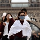 A woman wears a protective mask in light of the coronavirus outbreak in China as she walks at the Trocadero esplanade in front of the Eiffel Tower in Paris, France, February 1, 2020. REUTERS/Gonzalo Fuentes