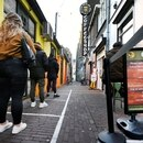 FILE PHOTO: Customers keep social distance while queuing outside a coffee shop, as they are allowed to reopen for cannabis takeaway sales, during the coronavirus disease (COVID-19) outbreak, in Nijmegen, Netherlands March 31, 2020. REUTERS/Piroschka van de Wouw/File Photo