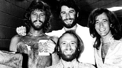 """Los Bee Gees con John Travolta, quien inmortalizó las canciones del grupo en la película """"Fiebre de sábado por la noche"""" (Shutterstock)"""