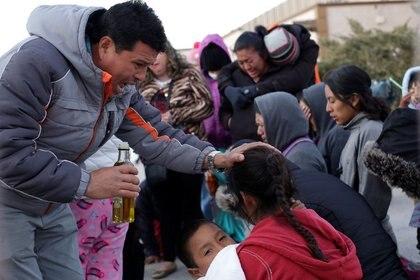 Migrantes rezan en el albergue Leona Vicario, en la fronteriza Ciudad Juárez, cerrado temporalmente por las autoridades de salud tras un brote de varicela entre migrantes centroamericanos enviados a México desde Estados Unidos, mientras se desahogan sus casos de asilo. México, 27 de diciembre de 2019. REUTERS / José Luis González