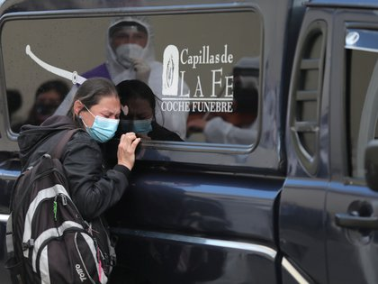 A woman wearing a face mask leans on a hearse where the body of one of her relatives, who allegedly died of the coronavirus disease (COVID-19), is lying, amidst an outbreak of the coronavirus disease (COVID-19), in Bogota, Colombia August 10, 2020. Picture taken August 10, 2020. REUTERS/Luisa Gonzalez