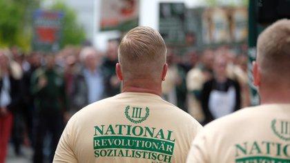 """Partidarios del partido neonazi y de extrema derecha """"Der Dritte Weg / Der III Weg"""" (El tercer camino / El III camino) caminan por Plauen, en el este de Alemania.  (Photo by Sebastian Willnow / dpa / AFP) / Germany OUT"""