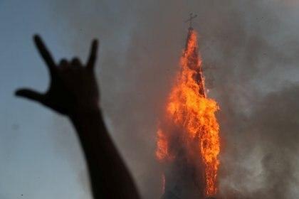 Un manifestante gesticula mientras una iglesia se incendia durante una protesta contra el gobierno de Chile, en el primer aniversario de las protestas y disturbios que sacudieron la capital en 2019, en Santiago, Chile. REUTERS/Ivan Alvarado