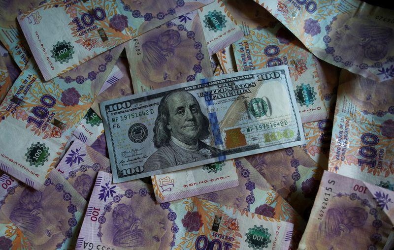 FOTO DE ARCHIVO: Un billete de cien dólares estadounidenses reposa sobre billetes de cien pesos de Argentina en esta ilustración fotográficatomada el 3 de septiembre, 2019. REUTERS/Agustin Marcarian/Illustration