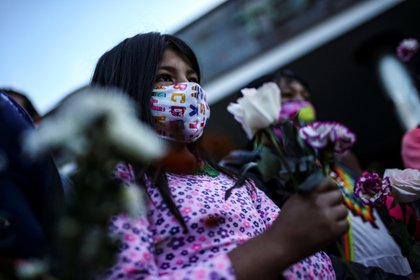 Demonstrators wearing face masks hold flowers during a protest in front of a military battalion, against the reported rape of an Embera Chami indigenous girl by soldiers, in Bogota, Colombia June 29, 2020. REUTERS/Luisa Gonzalez