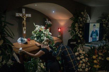 Anabel Garza Rivera y Luciano Leal Vela arrodillados ante el féretro de su hijo asesinado.