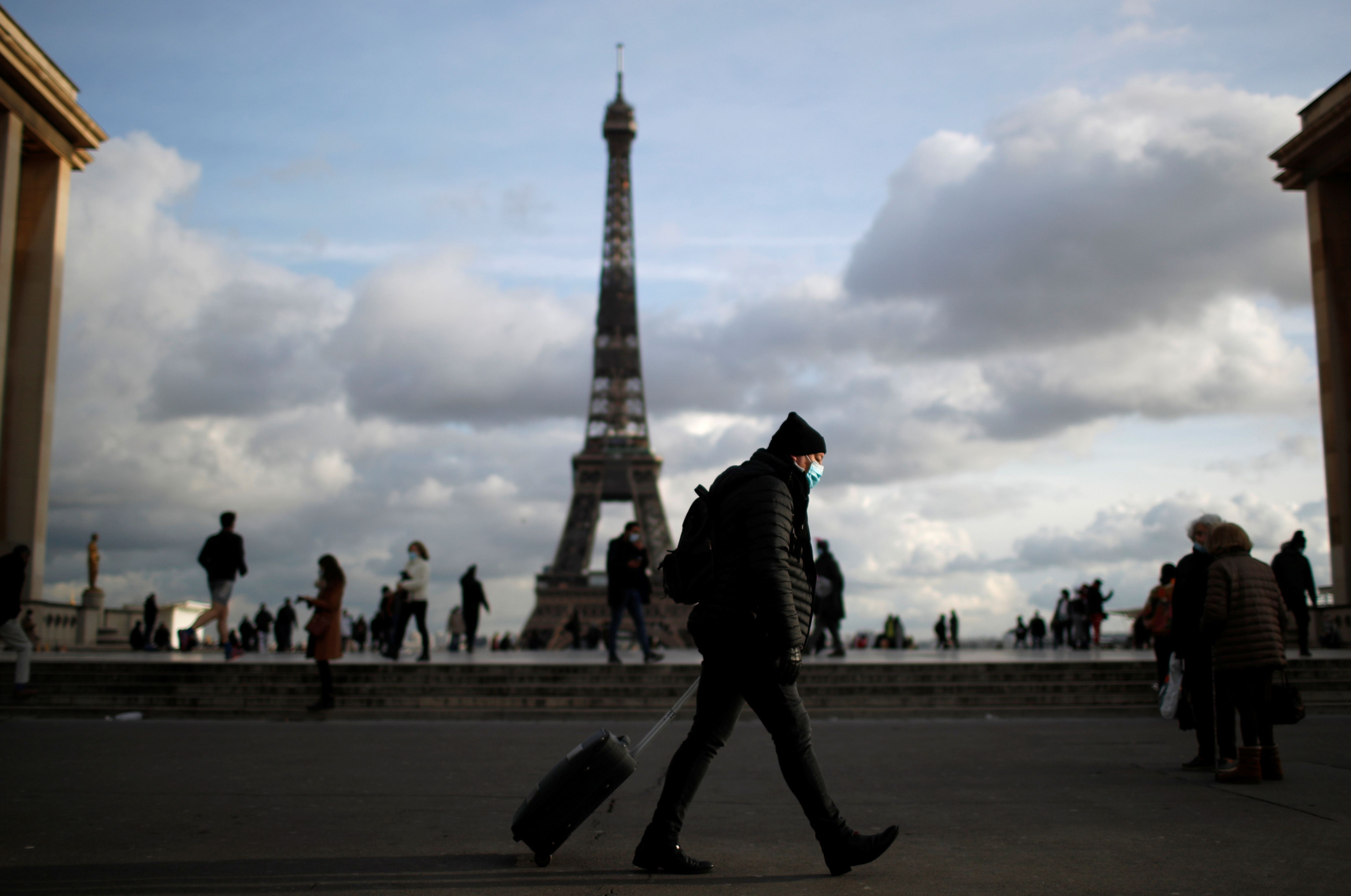 A man wearing a protective face mask walks at Trocadero square near the Eiffel Tower in Paris amid the coronavirus disease (COVID-19) outbreak in France, January 22, 2021. REUTERS/Gonzalo Fuentes