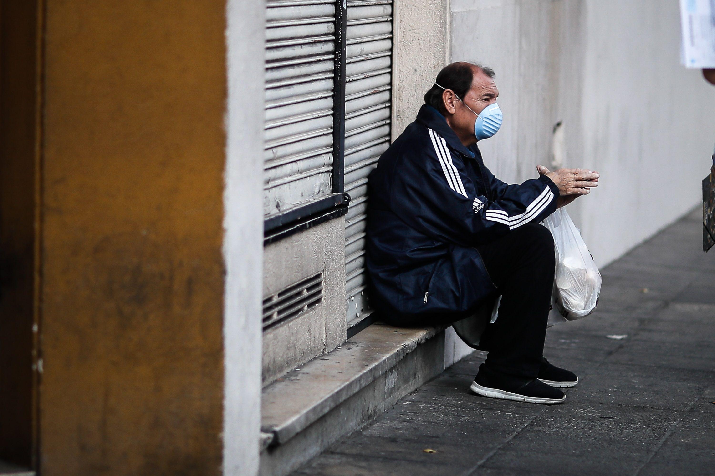 Un hombre protegido con tapabocas espera sentado durante una jornada de tomas de pruebas de coronavirus en Buenos Aires (Argentina). EFE/Juan Ignacio Roncoroni