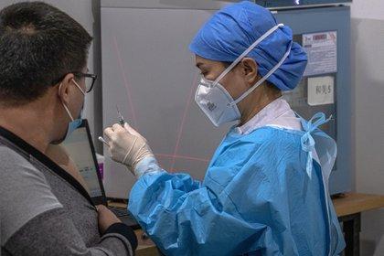 Un trabajador de la salud se prepara para vacunar a un hombre con la vacuna Sinopharm en un centro de vacunación en Pekín, China (EFE/EPA/ROMAN PILIPEY/Archivo)