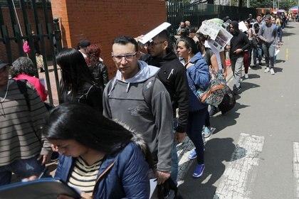 Photo de fichier.  Des gens font la queue pour remplir des demandes d'emploi tout en recherchant des opportunités d'emploi à Bogotá, Colombie, le 31 mai 2019. REUTERS / Luisa González