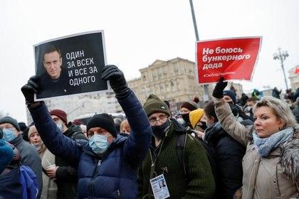 """Un hombre sostiene una pancarta en la que se lee """"Uno para todos, todos para uno"""" durante una manifestación de apoyo al líder opositor ruso encarcelado Alexei Navalny en Moscú, Rusia, el 23 de enero de 2021. REUTERS/Maxim Shemetov"""