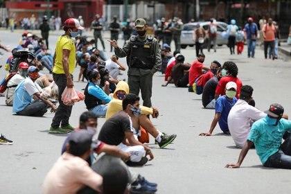 Un miembro de la Guardia Nacional de Venezuela entre un grupo de personas sentadas bajo el sol por no cumplir con las normas de salud por la pandemia de coronavirus en una calle en Caracas. Ago 5, 2020. REUTERS/Manaure Quintero