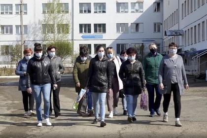 Enfermeras y ayudantes médicos caminan para encontrarse con periodistas frente a un hospital en la ciudad rusa de Chita, en Siberia (Foto AP / Konstantin Vasilyev)