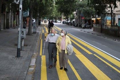 Un matrimonio de ancianos con mascarillas pasea por una franja de color pintada para el uso de peatones a fin de mantener el distanciamiento social, durante el brote de la enfermedad del nuevo coronavirus (COVID-19) en Barcelona, España, el 11 de mayo de 2020. REUTERS/Nacho Doce